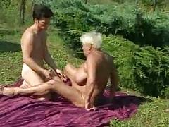 Granny fucks outdoors